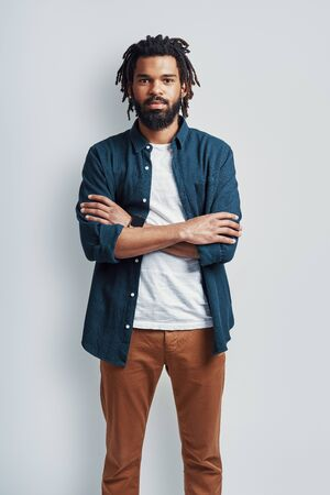 Thoughtful young African man in casual wear looking at camera and keeping arms crossed while standing against grey background Archivio Fotografico