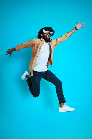 Full length of playful young African man wearing virtual reality glasses while hovering against blue background