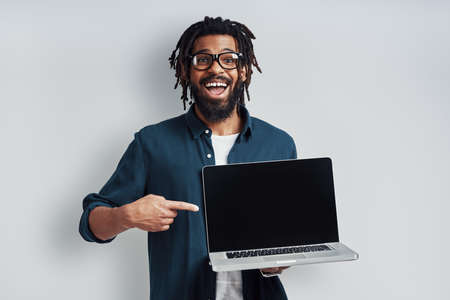 Charming young African man in eyewear pointing copy space on laptop while standing against grey background