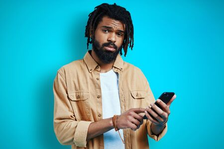 Charming young African man in casual clothing using smart phone and looking at camera while standing against blue background