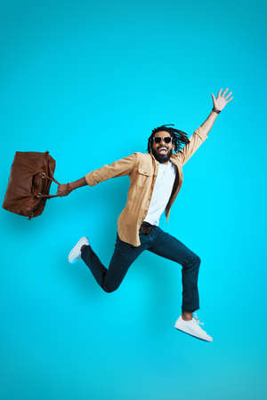 Full length of stylish young African man in casual wear smiling and carrying bag while hovering against blue background