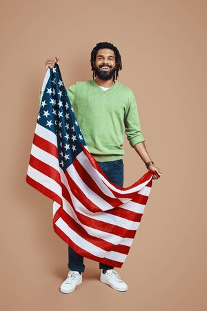 Full length of happy young African man covered in American flag looking at camera and smiling while standing against brown background
