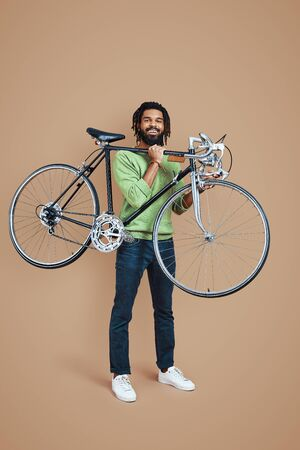 Full length of young African man in casual clothing looking at camera and carrying bicycle while standing against brown background