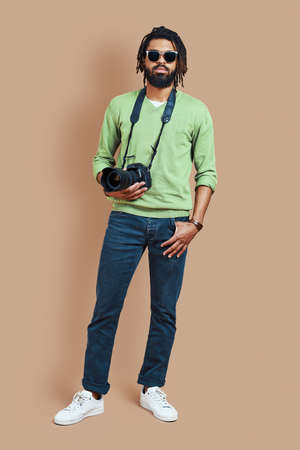 Full length of young African photographer in casual clothing looking at camera while standing against brown background 免版税图像