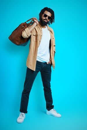 Full length of young African man in casual wear carrying leather bag and looking at camera while standing against blue background