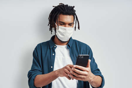 Careful young African man wearing medical face mask and using smart phone while standing against grey background
