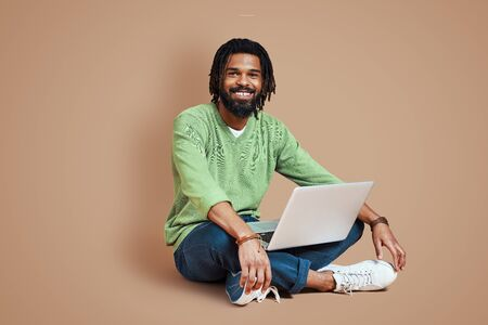Handsome young African man in smart casual clothing using laptop and smiling while sitting against brown background 免版税图像