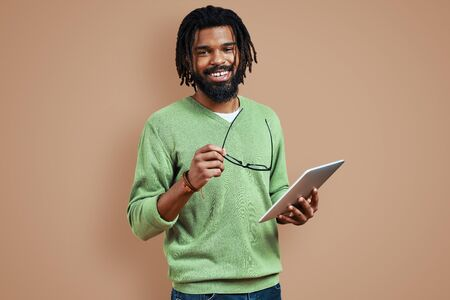 Smiling young African man in smart casual clothing using digital tablet and looking at camera while standing against brown background