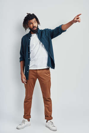 Full length of charming young African man in casual wear pointing copy space while standing against grey background
