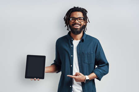 Charming young African man in eyewear pointing copy space using digital tablet while standing against grey background