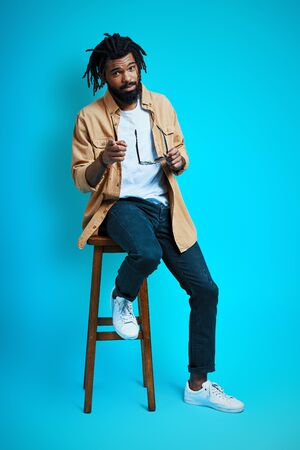 Full length of trendy young African man in casual wear looking at camera and pointing you while sitting on stool against blue background