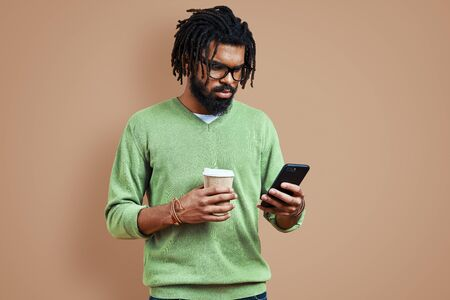 Busy young African man in smart casual clothing using smart phone while standing against brown background