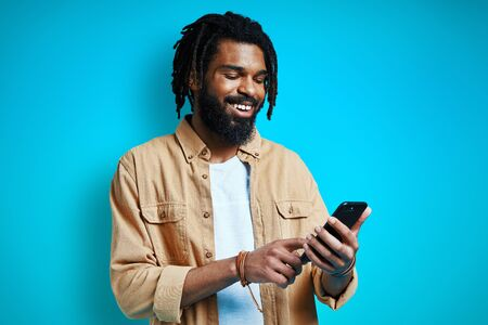 Handsome young African man in casual clothing using smart phone and smiling while standing against blue background