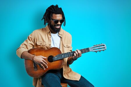 Charming young African man in casual wear playing the guitar and smiling while sitting against blue background