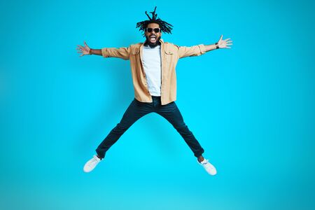 Full length of happy young African man in casual wear keeping arms and legs outstretched while hovering against blue background 免版税图像