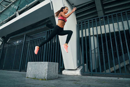Full length of attractive young woman in sports clothing hovering in a long jump while exercising outdoors