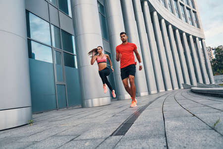 Full length of confident fit couple in sports clothing enjoying morning jogging while practicing outdoors on the city street