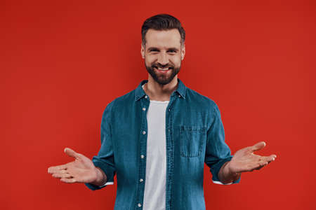 Good looking young man in casual clothing keeping arm outstretched and looking at camera while standing against red background Stockfoto