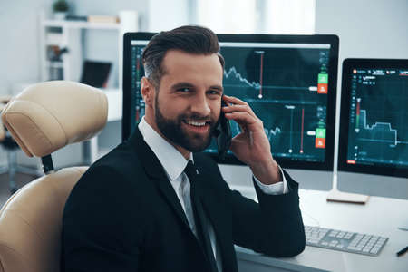 Handsome young man in shirt and tie talking on the phone and smiling while working in the office