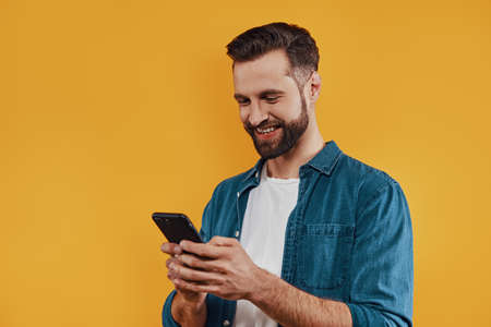 Charming young man in casual clothing using smart phone and smiling while standing against yellow background Stockfoto