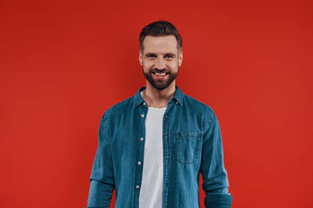 Handsome young man in casual clothing smiling and looking at camera while standing against red background