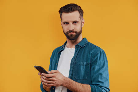 Good looking young man in casual clothing using smart phone and looking at camera while standing against yellow background