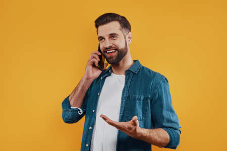 Handsome young man in casual clothing talking on the smart phone and smiling while standing against yellow background Stockfoto
