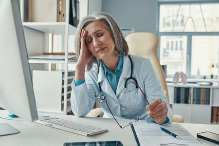 Tired mature female doctor in white lab coat keeping eyes closed while sitting in her office
