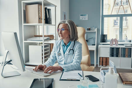 Confident mature female doctor in white lab coat working on computer while sitting in her office Stockfoto