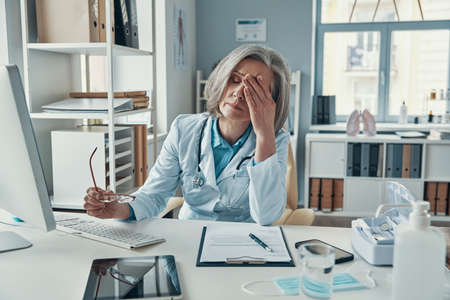 Tired mature female doctor in white lab coat covering her face with hand while sitting in her office Stockfoto