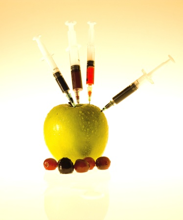 Apple with an injectors on it Stock Photo