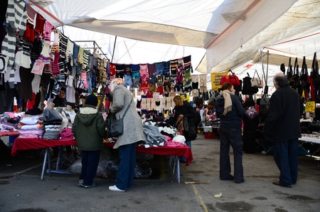 Istanbul, Turkey � November 19, 2011: Turkish people are shopping at local opened air bazaar. Saling goods are more cheaper than shops at this local bazaar.