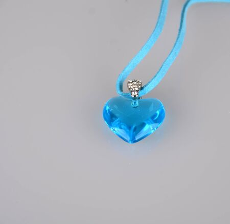 Light blue necklace was shot on gray surface