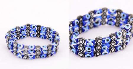 b�se augen: Handmade Armband wurde von b�sen Augen der traditionellen t�rkischen Perlen auf wei�em Hintergrund Schuss gemacht Lizenzfreie Bilder