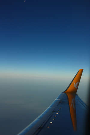 Adana, Turkey-March 03, 2011  Commercial airplane�s wing was shot while descending to Adana, by company logo  Nice view of sky   Reflection of company logo on wing