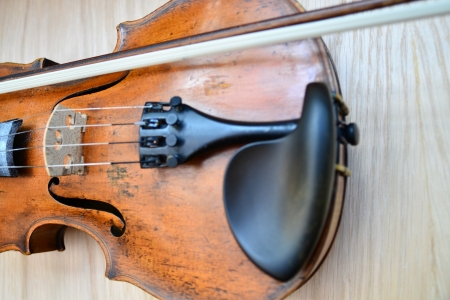 Violin and bow are standing on wooden surface  photo