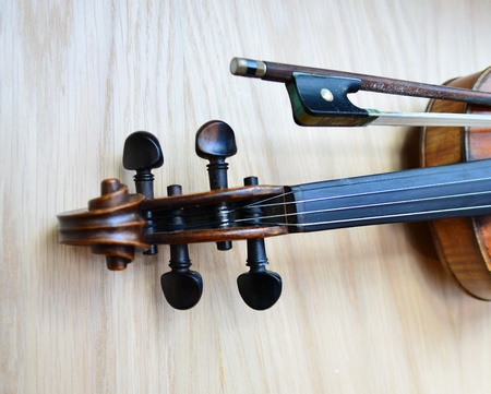 Neck part of a violin shot on wooden surface