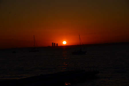 Sun gets down over the sea in dark evening