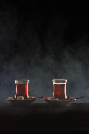 Turkish traditional tea serving on black in smoke  Stock Photo