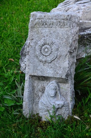 Flower and mother symbols are on ancient stone.