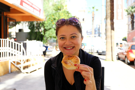 Middle aged blonde female holds a traditional bagel to eat.