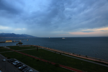 Konak, Izmir, Turkey – March 31, 2017: On a nice afternoon people were walking next to coast in Izmir, Turkey. Ships were parked near to city. Izmir is a city which located on Mediterranean Sea.