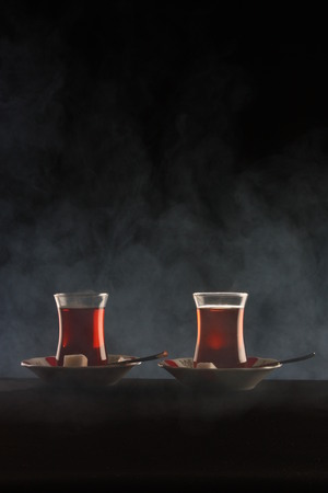 Turkish traditional tea serving on black in smoke. Stock Photo