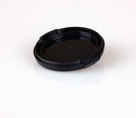 Black colored lens cap shot on white background. Stock Photo