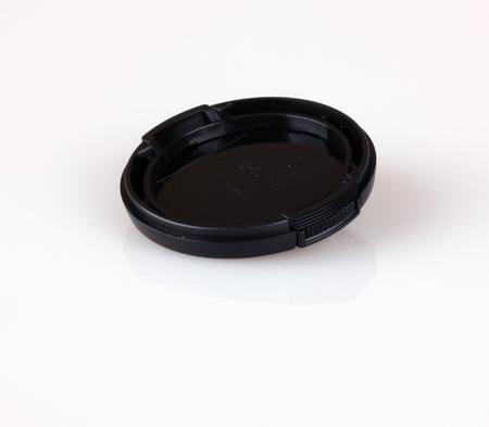 Black colored lens cap shot on white background. Banco de Imagens
