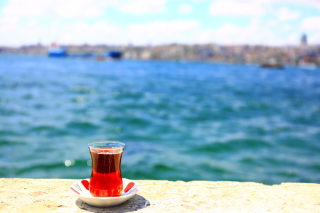 It is leisure time next to Istanbul Bosphorus watching sea and drinking traditional Turkish tea. Banco de Imagens - 102025840