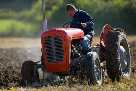 harrow: Old Tractor ploughing field Stock Photo
