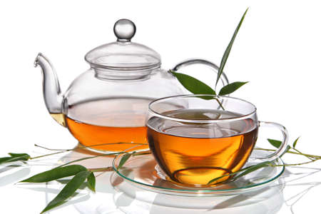 Cup of tea with teapot and bamboo leaves, isolated on a white background