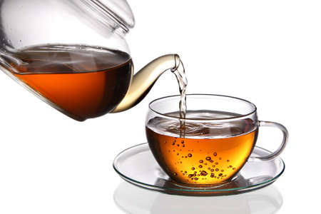 whitern: Tea being poured into glass tea cup isolated on a white background