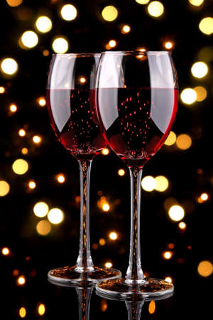 Glasses of red wine with bokeh light effect